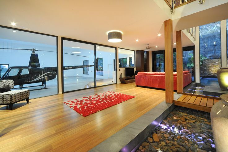 Chris Clout Design hangar home in Whitsunday's with helicopter in house modern contemporary tropical with good lighting pool comes into house with good interiors