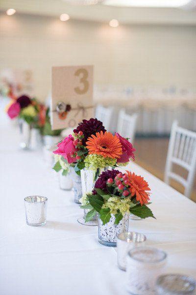 Bright centerpiece option - gerbera daisies, berries, dahlias, roses, and more displayed in mercury glass vessels {Kelly Brown Weddings}