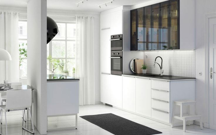 A modern white METOD kitchen with RINGHULT high-gloss white fronts, HÄLLESTAD black worktops and JUTIS smoked glass doors