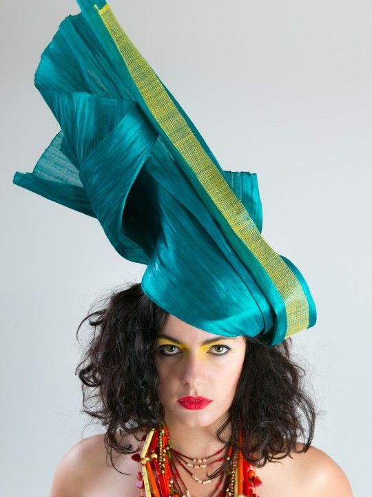 AFFRIKANZ   Silk Hat for 2013 Spring Racing Carnival   FORD MILLINERY  $675  Stunning hand-cafted headpiece with tribal influences. Jade abaca silk fabric is seemingly frozen mid-flow, trimmed with earthy-cut yellow sinamay. Mounted on a sinamay base with a metallic hair-comb for structural-engineering confidence. Each Affrikanz headpiece is slightly different to the next, as we follow the silk where she wants to go. Perfectly teamed with a bold print or trbal influenced jewellery.