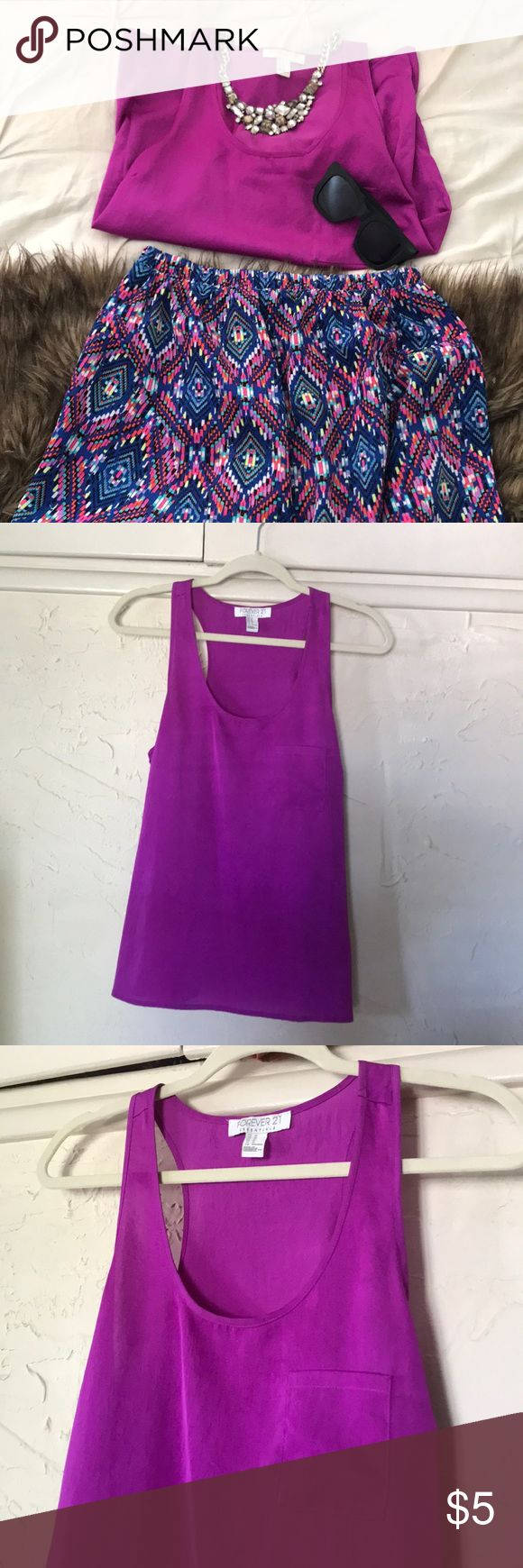 Magenta racer back tank by Forever 21, size Medium Super cute magenta, racer back tank from Forever 21, size Medium. 100 % polyester, feels like silk. Dress it up with a skirt and heels or down with jeans and statement necklace! Forever 21 Tops Tank Tops