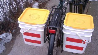 You can construct a set of bicycle panniers in under an hour using two kitty litter buckets, hardware-store hooks, and reflective tape along with a cordless drill and a nuts and bolts. This will yield cheap efficient storage that can also ugly your bike to discourage theft.