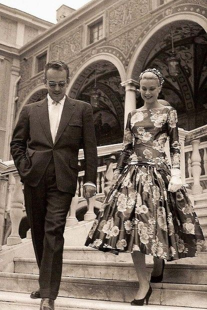 Grace Kelly & Prince Rainier on the day of their first meeting. (Grace actually hated that dress! It was the only one she had that didn't need to be ironed since that morning, her hotel had an blackout. That meant she couldn't do her hair either, so she had to wear the flower cap also. She was mortified through her visit, but Prince Rainier liked what he saw anyway.)