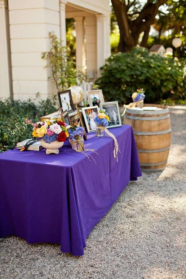 Vibrant purple tablecloths with rustic wedding decor and colorful floral decor and picture frames for an outdoor wedding.