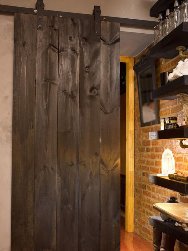 In keeping with his signature rustic, industrial style, Dan fabricated a custom barn door, then attached it to the living room wall outside the bedroom with iron track. To partition the sleeping area off from the living room when guests spend the night on the futon, the couple simply closes the barn door for instant privacy.