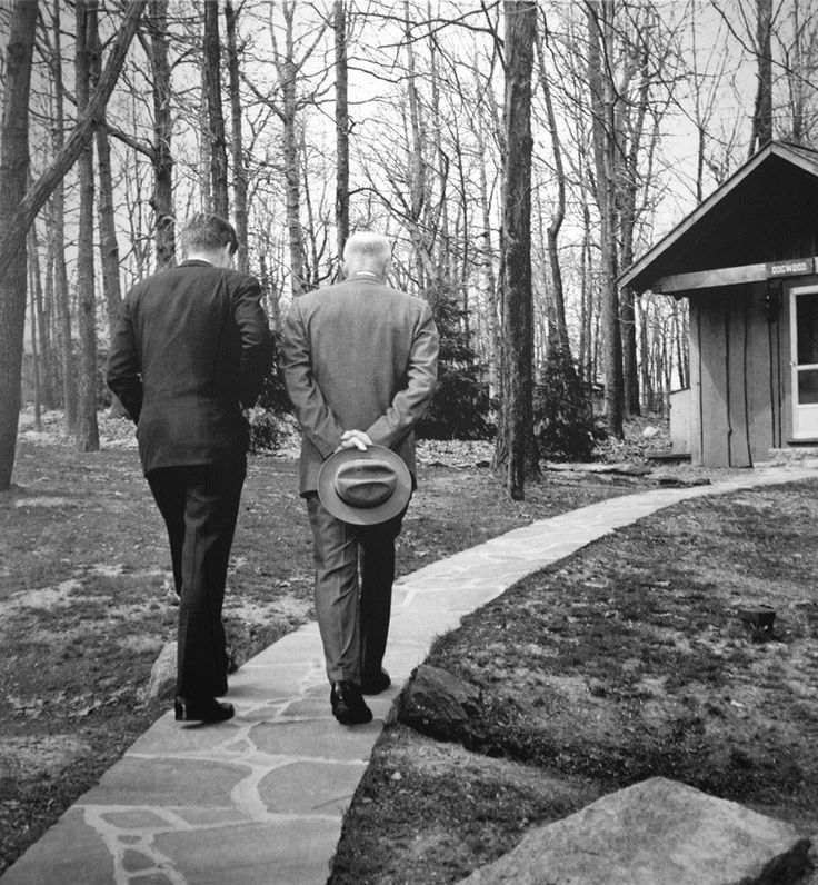 After the Bay of Pigs Invasion Kennedy Consults Eisenhower – 1962.  President John F. Kennedy and former president Dwight D. Eisenhower are having a wintertime walk at Camp David in winter.