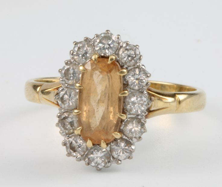 Lot 680, An 18ct yellow gold oval citrine and diamond cluster ring, the centre oval citrine surrounded by 12 brilliant cut diamonds, size P 1/2, sold for £360