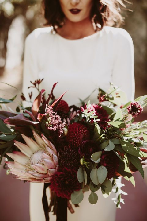Queen Protea, a show-stopping tropical flower, takes center stage in this deep red and green wedding bouquet. Surrounding the luxurious bloom are burgundy dahlias, scabiosa flowers, ranunculus, kangaroo paw, a mix of eucalyptus leaves and burgundy ti leaves. Via Junebug Weddings, The Bloomin Gypsy and Lauren Scotti