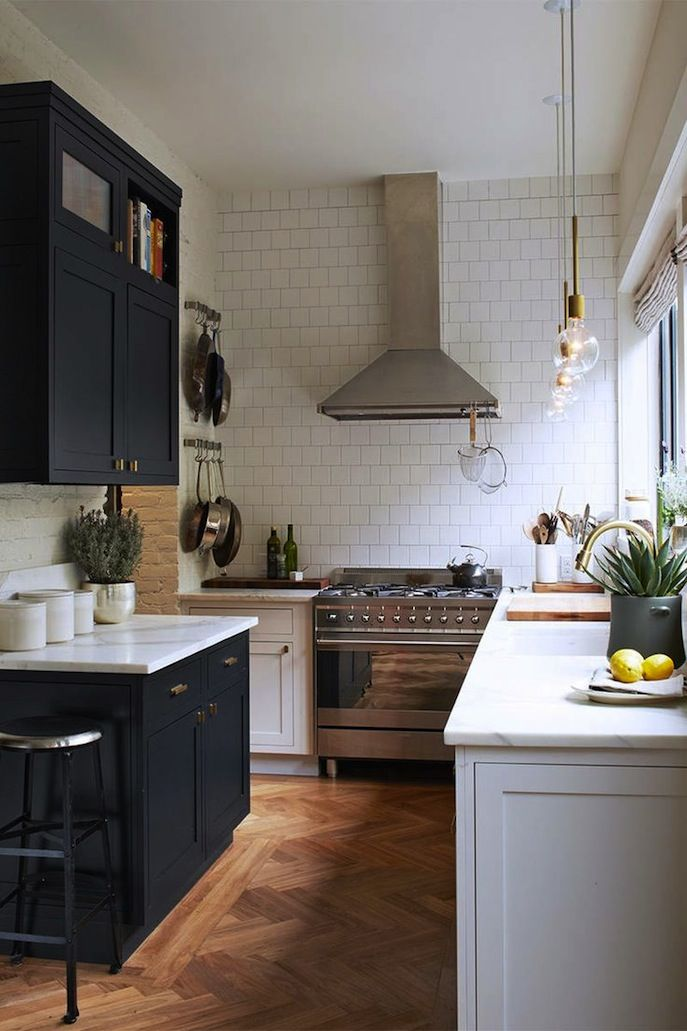 mix of dark and white cabinets/island + marble countertop + brass details and lighting