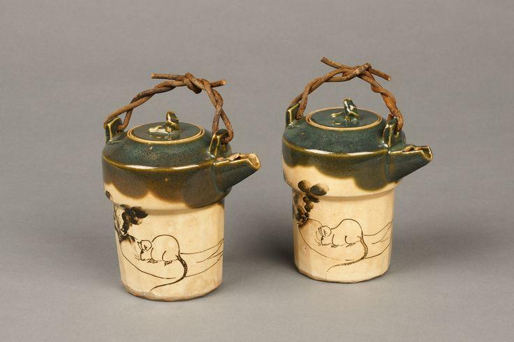 瑞芝焼 織部写銚子 2合(江戸時代19世紀、高12.3cm/底径7.7cm)。銚子は、酒をつぐ器で、上部に持ち手がある形式は、提子とも呼ばれた。携帯用としても使え、酒を温められるようになっている。上部に緑色の釉薬をかけ、下部の白い部分には褐色の釉薬で大根とねずみを描いている。この配色は、桃山時代から江戸時代にかけて美濃国(現在の岐阜県南部)で焼かれた織部焼をまねたもの。底に「瑞芝」の印が捺され、江戸時代後期に和歌山城下の鈴丸で焼かれた瑞芝焼であるとわかる。