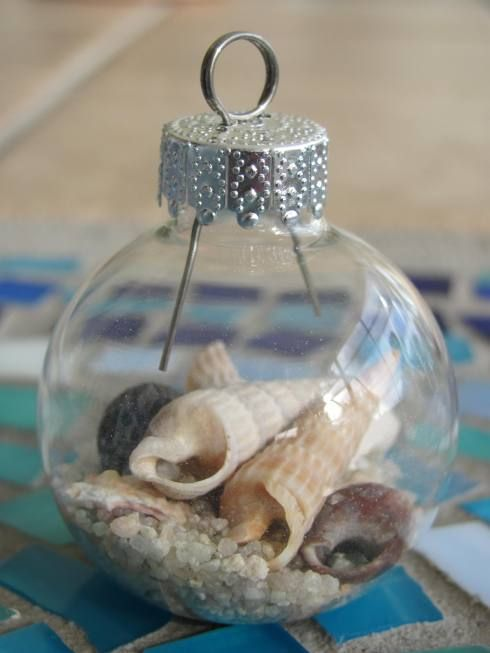 Make your own stunning nautical beach inspired Christmas ornaments by filling glass ornament balls with sand, tiny seashells, beach glass, raffia, tiny stones and nautical-inspired rope!