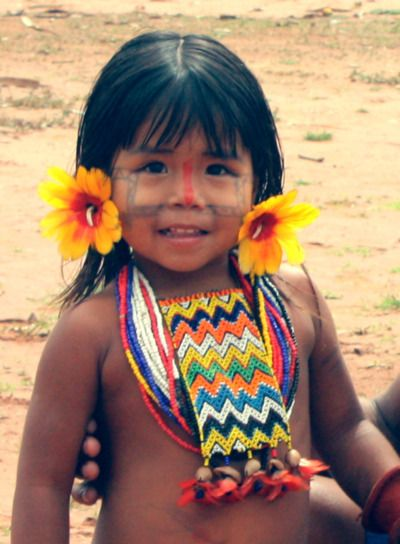 Karajá girl - Brazil....her ear rings aren't flowers? Close up, they appear to be feathers flared around protruding claws or curved objects.