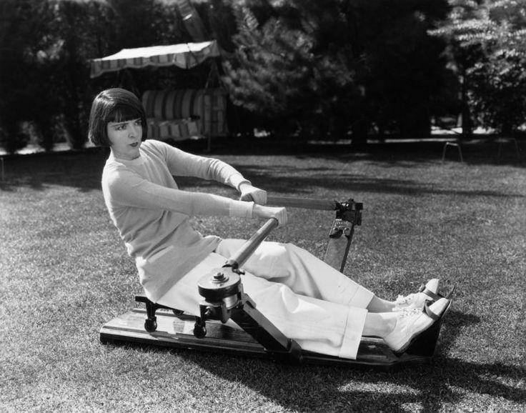 Stummfilmstar Colleen Moore (1900–1988) trainiert mit einer Rudermaschine im Garten. (circa 1928)