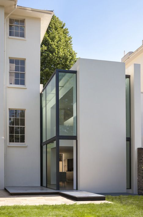 Narrow slices of glazing break up the plain white facade of this residential extension in west London by Guard Tillman Pollock Architects, helping to visually separate it from the existing house.