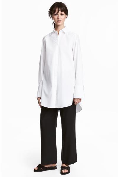 Calças largas em tecido de Tencel® lyocell com cintura de altura regular com elástico e cordão de ajuste. Tem bolsos laterais e bolsos atrás.
