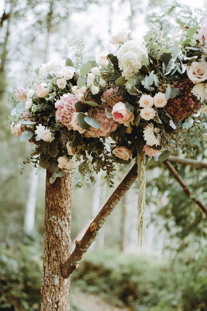flower-adorned tree branches make for a beautiful ceremonial arch  | Image by Anni Graham Photography
