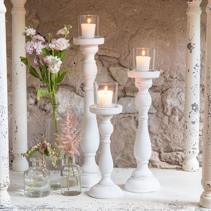 Shabby Chic Spindle Candle Holder Set WhiteThis set of candle holders features a shabby chic style, glass votives and three varied heights. Place all three together for an elegant centerpiece or space them out to provide a little light along each table.