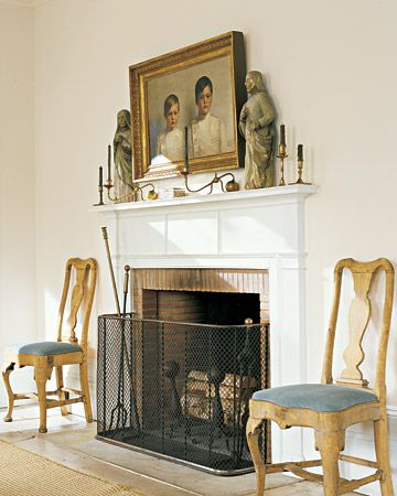 The living room walls and mantel were painted slightly different variations of the same color -- white with a touch of gray. The painting is a 1911 portrait of Swedish boys in school uniforms, and the statues came from a rustic church in southern Sweden. The candlesticks are an ingenious nineteenth-century English design with weighted bases that let the candles project in front of the mantel.