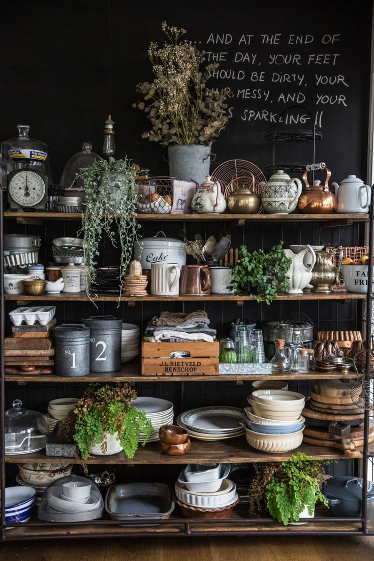 These shelves, wonderfully cluttered with delightful kicheney items, reminds me of Bilbo Baggins' pantry. There's something about it that is so pleasing to my eye. Gotta love the chalkboard wall, too.