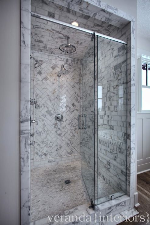 Marble Tiled Shower With Accent In Herringbone Pattern.