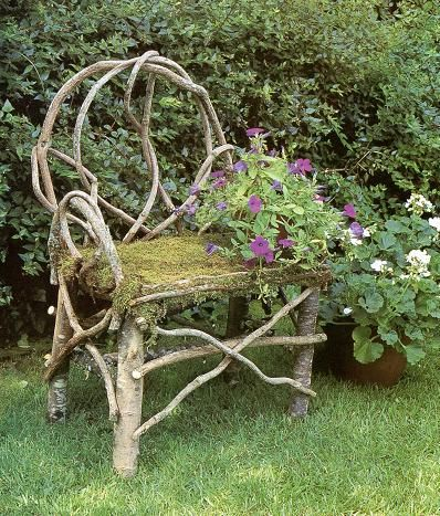 chair made from twigs of small trees with flowers growing up the side . How pretty!