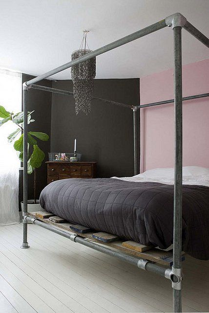 Industrial canopy pipe bed frame made with black pipe and Kee Klamp pipe fittings.