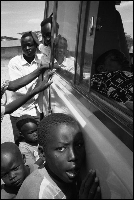 Eli Reed KENYA. Kakuma Refugee Camp. August 2001. Refugees surround a UN vehicle  Magnum Photos