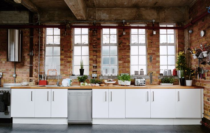 White kitchen in a London warehouse loft with exposed brick