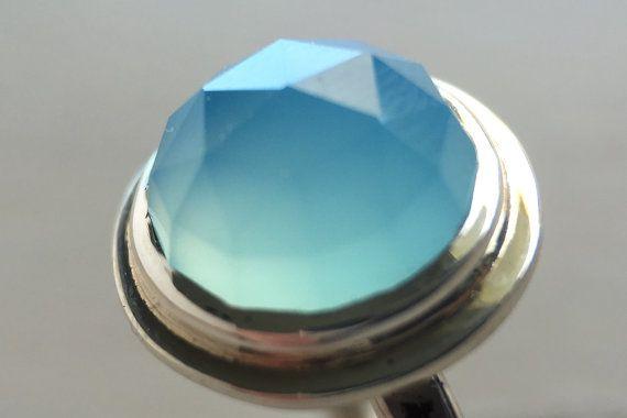 Gefacetteerd 10mm Oceaan Blauwe Chalcedoon instellen in sterling zilver. Een mooie, eenvoudige ring perfect voor het dragen van elke dag. De steen is neergestreken op de top van een ronde sterling draad schacht die heeft zijn gesmeed om een bijpassende faceted textuur. De steen in deze ring is hammerset. Hammersetting maakt gebruik van een dikke rand van fijn zilver die letterlijk naar beneden rond de steen is gehamerd. Niet alleen doet dit veilig greep het, het creëert ook een mooie halo…