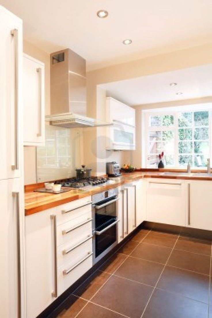 Modern white kitchen with wooden worktops and stainless steel appliances Stock Photo