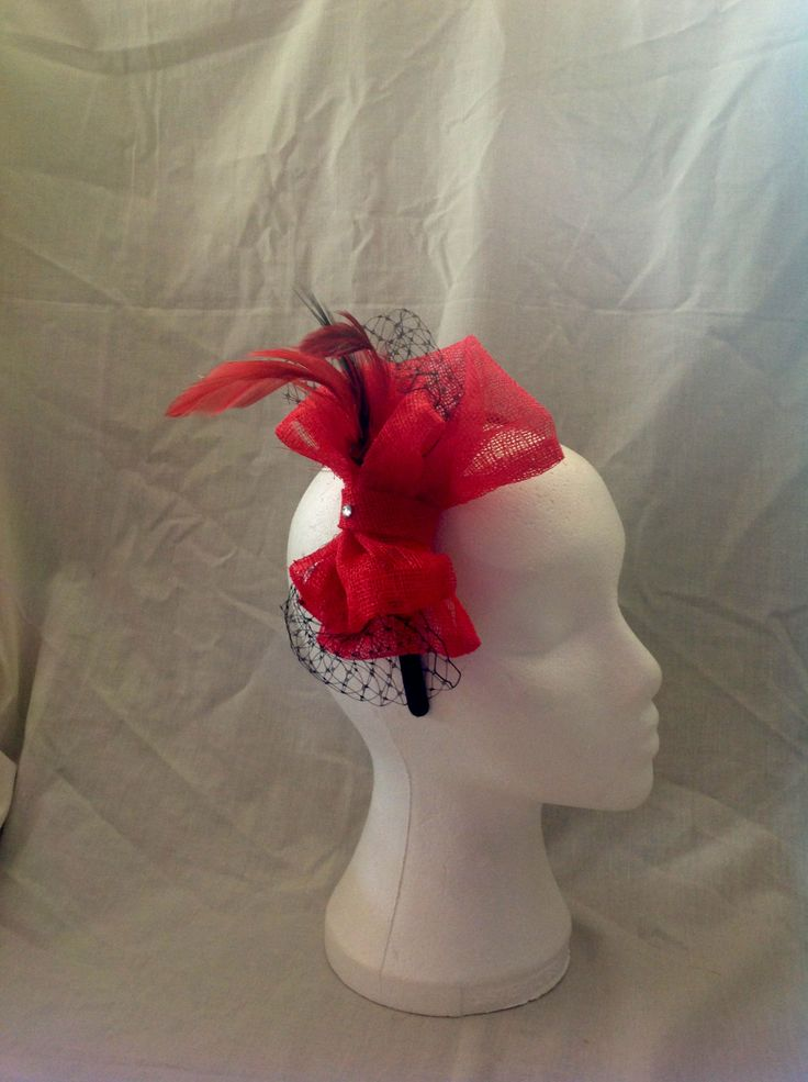The Lola is a medium fascinator on a black head band made up of two large ruby red diamante detailed sinamay bows suurounded by onyx black netting and matching feathers to finish. $80 AUD.