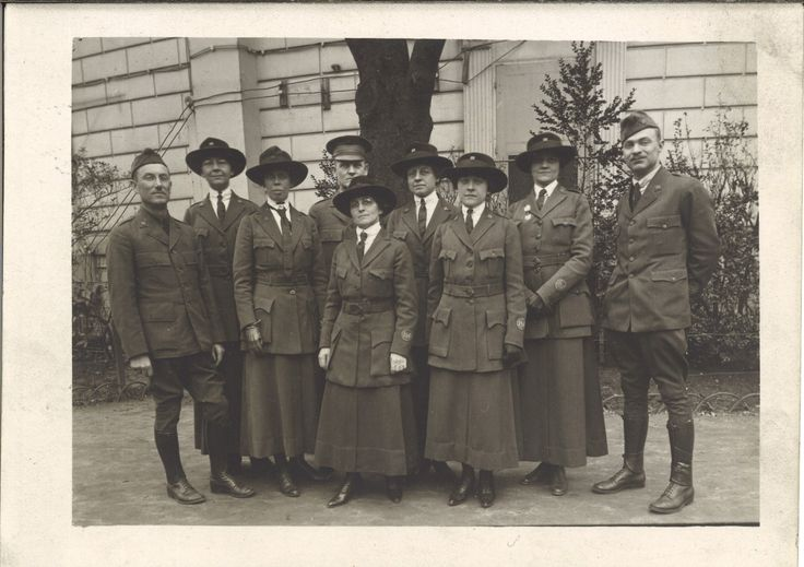 A group of librarians in matching uniforms, thigh-length coats over narrow pants or ankle-length skirts.
