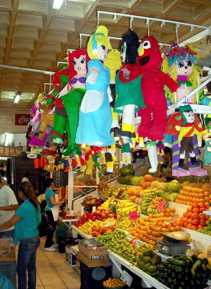 Enormous indoor market at Guadalajara, Mexico. This stall sold an odd combination of fruit and piñata.