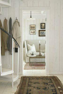 Soft white space with vintage accents. amazing rug against vertical boards.