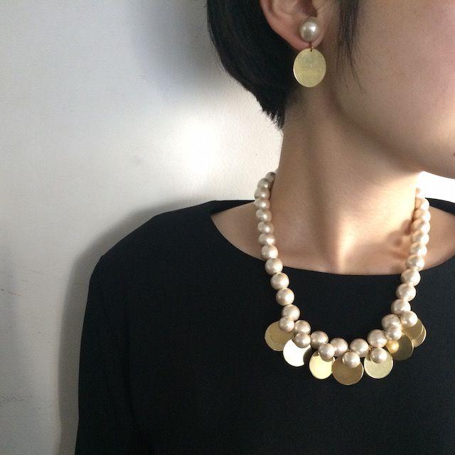 つややかな大粒パールに、輝きをおさえたゴールドのニュアンスがすてきな丸モチーフの重なりが印象的な、装うことが楽しくなるネックレス。
