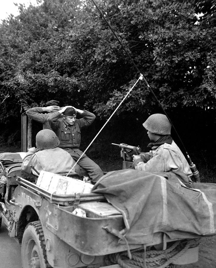 Two German prisoners of war are being taken to the 6th Division Prisoner of War Encampment for interrogation and searching. Plouay - north of Lorient, Brittany, France. 28th of August, 1944