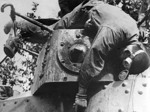The body of a Japanese tanker hangs over the turret of his Type 97 Te-Ke tankette after the Battle of Luzon - 1945