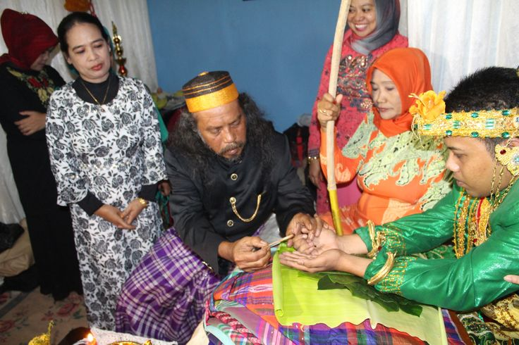 """""""mappacci"""" relatives of the groom coloring his hand,  coloring a hand with pacci leaves is a symbol of purity"""