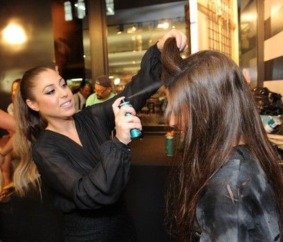 Behind the scenes of a fashion show, product is applied before final styling.