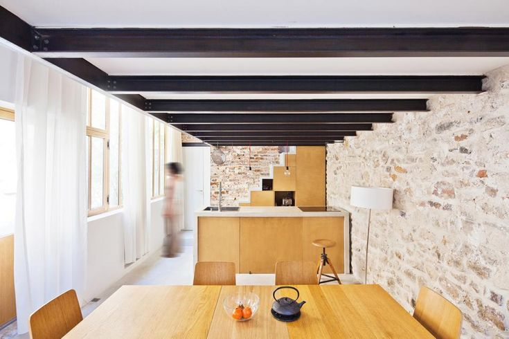 La muratura originale e le travi del soppalco danno alla casa un'atmosfera calda. Si tratta di un ex laboratorio artistico di 50 mq a Parigi ristrutturato dagli architetti Gianluca Gaudenzi e Sandra De Giorgio dello studio Nzi Architectes.