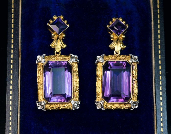 Belle Epoque Antique Carved Gold Platinum Amethyst Earrings - Circa 1910 - A pair of finely crafted antique 18K Gold dangle earrings is set with beautiful lavender and dark purple Amethysts. The Gold frames around the bigger Amethysts are carved with floral designs and accented at the corners with Fleur-de-Lys Platinum accents embellished with old rose-cut Diamonds. The larger Amethysts are approximately 7.15 ct and 7.10 ct. - $5,800.00