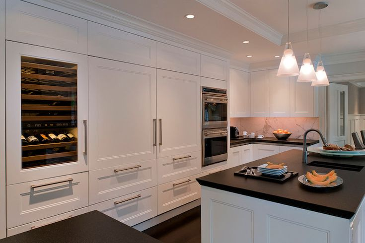 Incredible kitchen with wall of cabinetry framing a glass front wine cooler beside a concealed refrigerator with freezer drawers hidden behind paneled doors alongside stainless steel double wall ovens