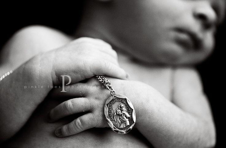 Wonderful newborn photography picture!  Baby holding the saint they were named after. This is very Catholic. And cute. Catholic and cute.