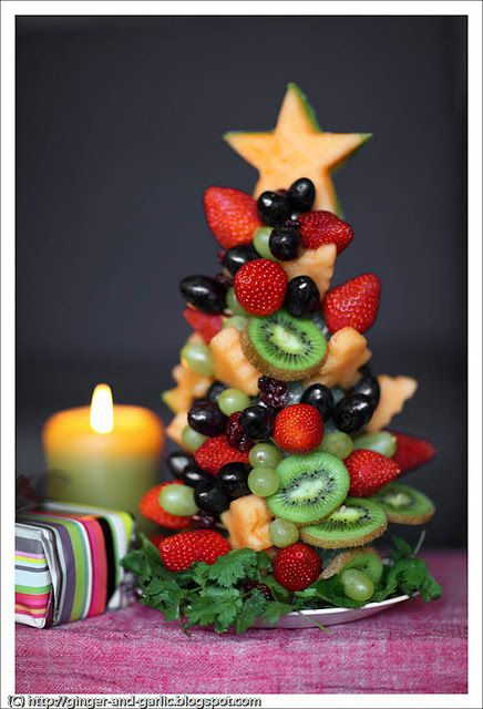 Edible Christmas tree centerpiece using styrofoam cone, toothpicks, various fruits, cookie cutters.