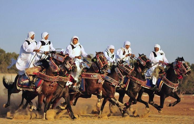 Men, dressed in traditional Libyan clothes, ride on horses during Eid al-Fitr in Benghazi, Libya.  (Esam Omran Al-Fetori / Reuters)
