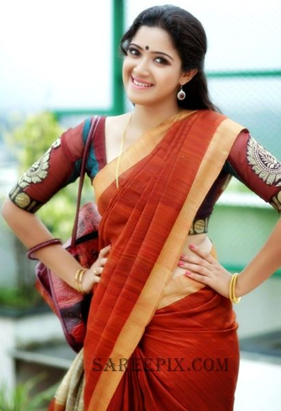 Actress Abhirami Suresh in saree photo. Cute smile with both hands on her waist made her look eye catchy.