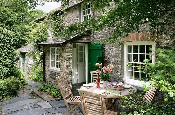 Love this stone house and patio with the neutral furniture. Also love love love the green door.