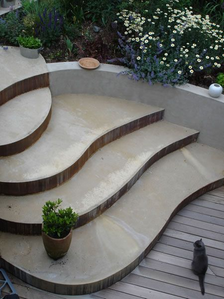 A stunning solution that creates an easy transition between basement kitchen to the main garden. The unusual, steel fronted, concrete steps are sinuous and fit snugly into the curved retaining wall.
