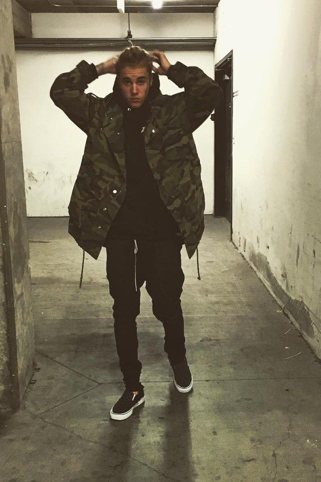 Justin Bieber wearing  Saint Laurent Oversized Patch Parka Camouflage Printed Cotton Gabardine, Vans Slip-On Sneaker, Fear of God Slim-Fit Drawstring Trousers