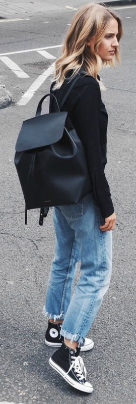 Ankle high converse look edgy and sleek when worn with ripped mom jeans and a casual black shirt. Via Mirjam Flatau.  Jeans: Levi, Shoes: Converse, Shirt: Rails. Easy to copy.